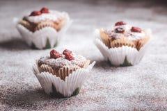 Muffins auf einem Holztisch bedeckt mit Zucker Stockfotografie