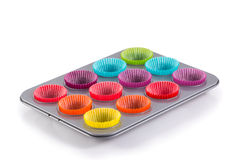 Muffins baking tray with colourful paper cases Royalty Free Stock Image