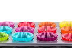 Muffins baking tray with colourful paper cases. Isolated on white royalty free stock photography