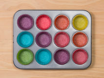 Muffins baking tray with colourful paper cases. On wooden background stock photography