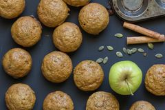 Muffins on black background with apple, cinnamon and pumpkin seeds - Top view image royalty free stock image