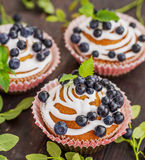 Muffins with blueberries, cream and fresh berries Stock Image