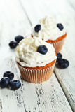 Muffins with blueberries and white cream on wooden background Royalty Free Stock Photos