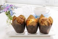 Muffins for breakfast. Breakfast table with three muffins in brown paper baking cups Stock Photos