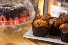 Muffins and cake on counter in coffee shop. Close-up of muffins and cake on counter in coffee shop stock photo