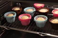 Muffins in ccolorful silicone molds growing up in the oven. Cupcakes, bakery. Close up royalty free stock photography