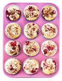 Muffins with Chocolade and Cherry in a pink colored baking tray Royalty Free Stock Photo