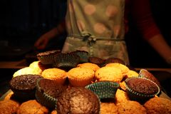 Muffins with chocolate and nuts. in the background a cook in an apron royalty free stock photo