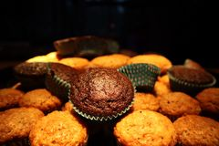 Muffins with chocolate and nuts. in the background a cook in an apron stock photo