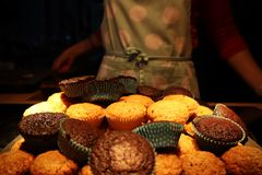 Muffins with chocolate and nuts. in the background a cook in an apron royalty free stock image