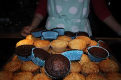 Muffins with chocolate and nuts. in the background a cook in an apron royalty free stock photography