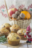 Muffins for Christmas carolers. Presented on a wooden board, with a traditional  tablecloth and a wicker basket with fruits and walnuts in the background Royalty Free Stock Photos