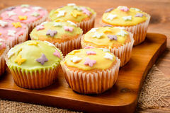 Muffins covered with colorful icing shugar on the wooden board. Royalty Free Stock Images