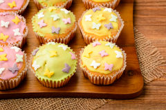 Muffins covered with colorful icing sugar. Royalty Free Stock Image