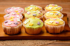 Muffins covered with colorful icing sugar on the wooden board. Royalty Free Stock Photo