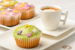 Muffins covered with icing sugar on white plate and cup of coffee. Royalty Free Stock Images