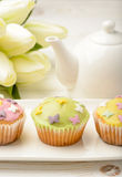 Muffins covered with icing sugar on white plate, tulips and tea pot on wooden table. Royalty Free Stock Photo