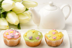 Muffins covered with icing sugar on white plate, tulips and tea pot on wooden table Royalty Free Stock Image