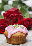 Muffins covered with pink icing and colorful sprinkles Stock Image