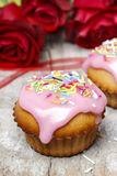 Muffins covered with pink icing and colorful sprinkles Royalty Free Stock Images