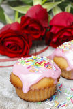 Muffins covered with pink icing and colorful sprinkles on wooden Stock Photos