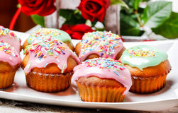 Muffins covered with pink icing and colorful sprinkles Stock Photography