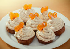 Muffins, cupcakes with cream and caramelized hearts Stock Photography