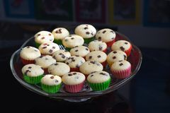 Muffins or cupcakes on the glass bowl or plate detailed Picture. Homemade muffins with chocolate pieces isolated. Stock Photos