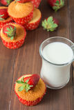 Muffins decorated with strawberry and glass of milk Stock Image
