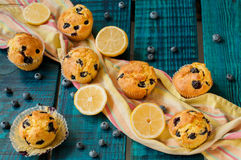 Muffins. Delicious muffins with blueberries. Decorated with fresh blueberries and lemon. Summer dessert on a blue background, which is stylized like old board Stock Image