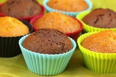 Muffins in den bunten kleinen Kuchen Stockbilder