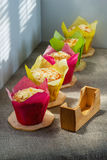 Muffins of different color on wooden supports a cloth. Muffins of different color on wooden supports on a cloth from rough fabric royalty free stock images