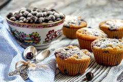 Muffins, eine Schale der schwarzer Johannisbeere und zwei silberne Löffel Lizenzfreies Stockbild