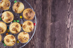 Muffins on a glass plate on a wooden background. Stock Photos