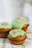 Muffins with green icing and colorful sprinkles Royalty Free Stock Images