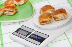 Muffins with ham and cheese on the digital kitchen scale Stock Image