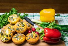 Muffins home made with pumpkin and sunflower seeds on wooden board and red and yellow pepper and green onions. royalty free stock photography