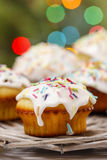 Muffins with icing and colorful sprinkles Stock Images