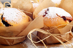 Muffins with jam sprinkled with powdered sugar. On wooden tray royalty free stock images