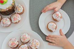 Muffins, kleine Kuchen mit Süßigkeiten auf einer weißen Platte und Kinderhände, Draufsicht lizenzfreies stockbild