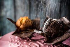 Muffins met gepoederde suiker worden bestrooid die Stock Fotografie