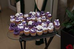 Muffins mit Sahne, süße Tabelle heiratend Purpurrote und weiße kleine Kuchen Set kleine Kuchen Bunte Sahnemuffins Lizenzfreie Stockbilder