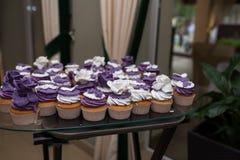 Muffins mit Sahne, süße Tabelle heiratend Purpurrote und weiße kleine Kuchen Set kleine Kuchen Bunte Sahnemuffins Stockfotografie