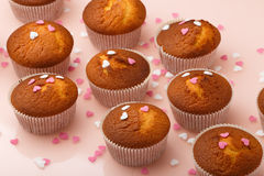 Muffins in paper forms and a lot of small sugar hearts on a mirrored background. Valentine`s Day breakfast Stock Photo
