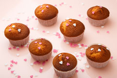 Muffins in paper forms and a lot of small sugar hearts on a mirrored background. Valentine`s Day breakfast Stock Photos