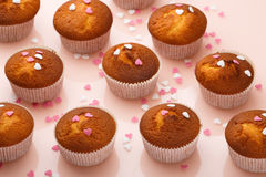 Muffins in paper forms and a lot of small sugar hearts on a mirrored background. Valentine`s Day breakfast Royalty Free Stock Photo