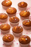 Muffins in paper forms and a lot of small sugar hearts on a mirrored background. Valentine`s Day breakfast Royalty Free Stock Image