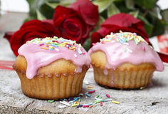 Muffins with pink icing and colorful sprinkles Stock Images