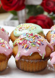 Muffins with pink icing and colorful sprinkles Stock Photo