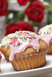 Muffins with pink icing and colorful sprinkles Stock Image